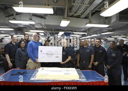 8  U.S. 5TH FLEET AREA OF OPERATIONS (June 3, 2017) Sailors from the sales and services division (S-3) of supply department and the Commanding Officer, Capt. Eric N. Pfister, pose for a group photo celebrating a donation they made to the ship's Morale, Welfare, and Recreation department of $100,000 earned from the ship's store and vending machines aboard the amphibious assault ship USS Bataan (LHD 5). The ship and its ready group are deployed in the U.S. 5th Fleet area of operations in support of maritime security operations designed to reassure allies and partners, and preserve the freedom of - Stock Photo