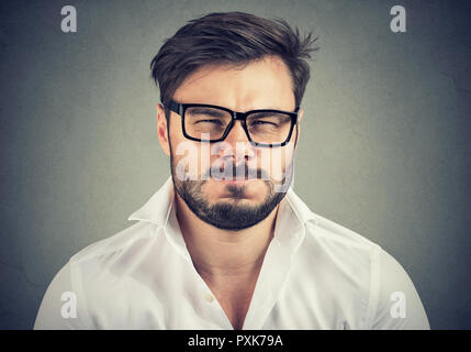 Portrait of bearded man in glasses and white shirt looking super annoyed and negatively at camera - Stock Photo