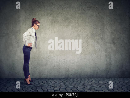 Side view of formal woman on high heels looking down in confusion being curious against gray background - Stock Photo