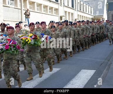 Berets and wreaths.  MONTEBOURG, France--More than 100 U.S. Army Soldiers, join the commanding general, French compatriots and people of Montebourg, France, during a march from the town center to the town's World War II memorial wall. Select Soldiers from 'Fighting Eagles,' 1st Battalion, 8th Infantry Regiment of the 3rd Armored Brigade Combat Team, 4th Inf. Div., participated in the march to the memorial dedication hosted by Maj. Gen. Ryan F. Gonsalves, commanding general of the 4th Inf. Div., Monteburg civic leaders, French compatriots and veterans. The Soldiers of 3rd ABCT are currently dep - Stock Photo