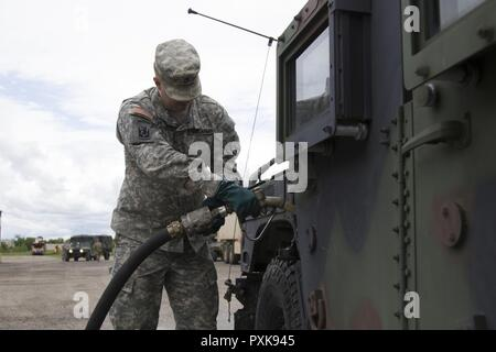 U.S. Army Staff Sgt. Henry Peterman, Headquarters, Headquarters Company, 86th Infantry Brigade Combat Team (Mountain), Vermont National Guard, fuels a Humvee in Malone, N.Y., June 4, 2017. Soldiers convoyed to Fort Drum, N.Y., for a brigade warfighter exercise during annual training. - Stock Photo