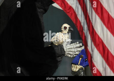 Bird skeleton in the hands of the grim reaper as a Halloween decoration displayed on a front lawn. - Stock Photo