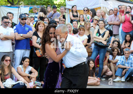 An older man and a younger woman dance tango before an audience in the plaza of San Telmo, Buenos Aires, Argentina - Stock Photo