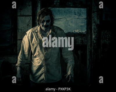 Photo of a zombie standing in a dark scary room. - Stock Photo