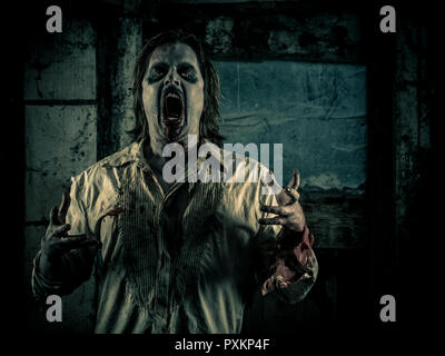 Photo of a hungry zombie staring at you in a dark scary room. - Stock Photo