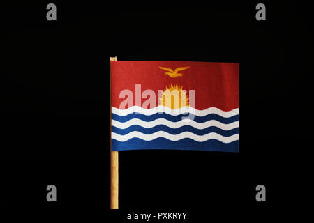 A official Flag of Kiribati on wooden stick on black background. State in the middle Oceania, pacific ocean. Sailing sun on sea. - Stock Photo
