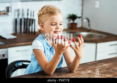 cute happy kid sitting at table and looking at ripe fresh raspberries on fingers - Stock Photo