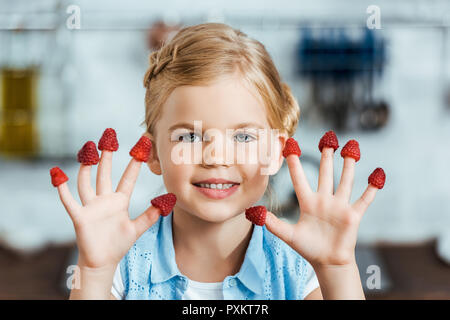 cute happy child with fresh ripe raspberries on fingers smiling at camera - Stock Photo