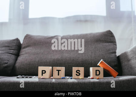 wooden cubes with posttraumatic stress disorder abbreviation signs (PTSD) lying on couch with various pills - Stock Photo