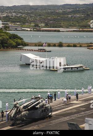 PACIFIC OCEAN (June 17, 2017) Sailors man the rails as the Nimitz-class aircraft carrier USS Carl Vinson (CVN 70) passes the USS Arizona Memorial during a tiger cruise. The tiger cruise allowed friends and family members of Sailors to embark the ship to experience U.S. Navy life at sea. - Stock Photo
