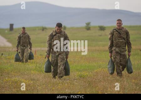 U.S. Army Soldiers, assigned to Multinational Battle Group-East, carry sand bags during The Best Three-Soldier Competition on Camp Bondsteel, Kosovo, June 17. The competition tested Soldiers on marksmanship skills, physical fitness, and knowledge of basic first aid skills. - Stock Photo