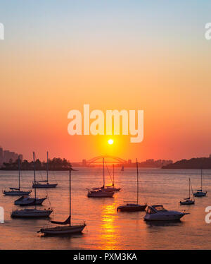 A beautiful sunset over Sydney  Harbour Bridge reflected in the tranquil waters of Hermit Bay in Vaucluse.Viewed from the Hermitage Foreshore Walk - Stock Photo