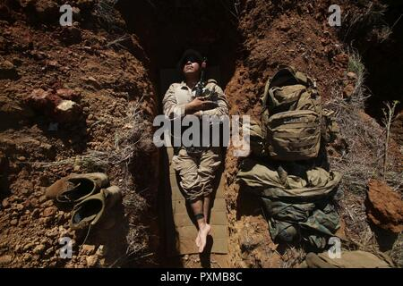 QUEENSLAND, Australia – Lance Cpl. Andrew Naranjo, a rifleman with 2nd platoon, Company L, 3rd Battalion, 4th Marine Regiment, 1st Marine Division, Marine Rotational Force Darwin, lies in his fighting hole during Exercise Brolga Strike, June 5th, 2017. Marines with 3rd Bn., 4th Marines, hiked more than 100 kilometers during the first week of exercise. Marines trained with Australian Defence Forces during the two-week brigade certification exercise. - Stock Photo
