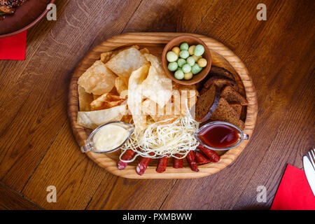 A board with snacks for beer. Board with chips, sausages, rye bread, cheese and red and white sauce. On a wooden table - Stock Photo