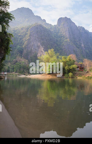 Scenic view of limestone karst mountains and the Nam Song River near Vang Vieng, Vientiane Province, Laos, on a sunny day. - Stock Photo