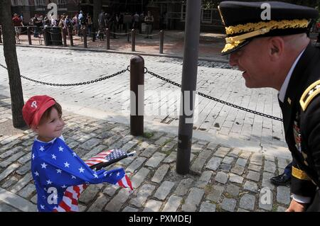 Maj. Gen. Troy D. Kok, commanding general of the U.S. Army Reserve's 99th Regional Support Command, greets a small child wearing an American flag prior to the start of the Stripes and Stars Festival celebrating the U.S. Army 242nd birthday at Independence Hall in Philadelphia. - Stock Photo