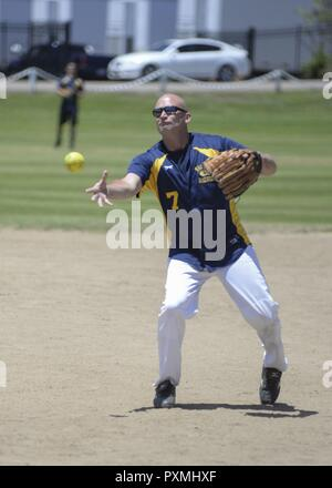 SAN DIEGO (June 13, 2017) Lt. Cory Prenatt, assigned to amphibious assault ship USS Boxer (LHD 4), throws a pitch during a softball game for Gator Week at Admiral Baker Park. Gator Week is an annual event hosted by Expeditionary Strike Group Three. The week consists of various sporting events and competitions, culminating with the Gator Ball. The event is designed to build camaraderie and teamwork across the strike group. - Stock Photo