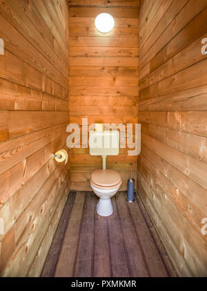 Wooden alpine toilet area in eco camp resort. - Stock Photo