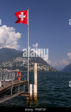 Swiss flag at Lugano on Lake Lugano, Switzerland - Stock Photo