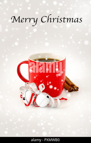Red Christmas mug filled with black coffee and decorated with white jingle bells, silver metallic ribbon, cinnamon sticks and snowfall. Merry Christma - Stock Photo