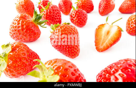 Closeup of fresh, vibrant strawberries with green stems on white background. - Stock Photo
