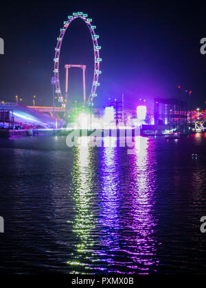 Singapore Flyer, the ferris wheel at Singapore Marina Bay, at night. - Stock Photo