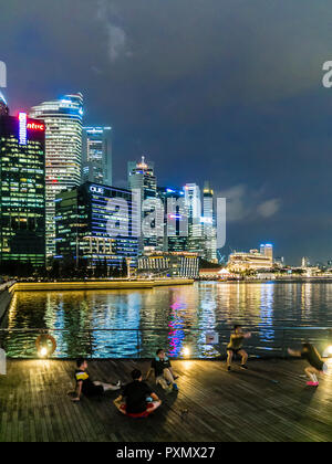 People are sitting at the quay of Singapore Marina Bay in the evening. - Stock Photo