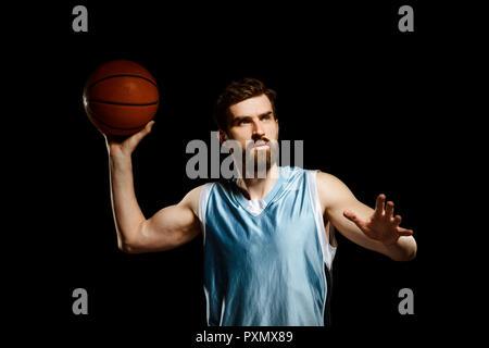 Handsome basketball player shooting ball