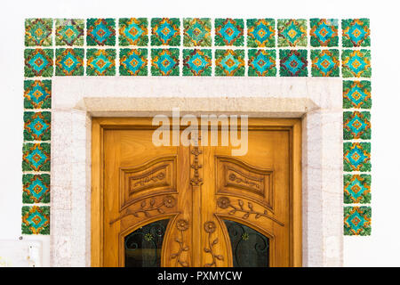 Door decorated with green azulejos, Ericeira, Lisbon Coast, Portugal - Stock Photo
