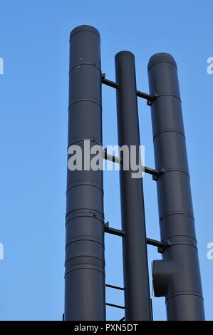 dark painted metal chimney pipes towering into blue sky - Stock Photo