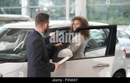 Car dealer standing with client near car and giving keys. Beautiful happy woman holding hand and taking keys from manager. Female customer buying white automobile in car center. - Stock Photo