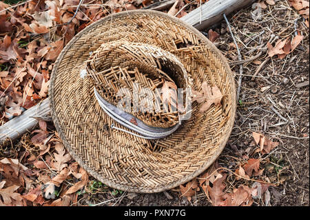 An old woven straw hat on a bed of brown autumn leaves. - Stock Photo