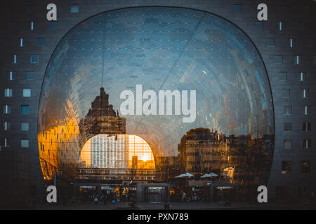 Reflection of cityscape in Rotterdam on the facade of Market Hall (Markthal) during golden hour - Stock Photo