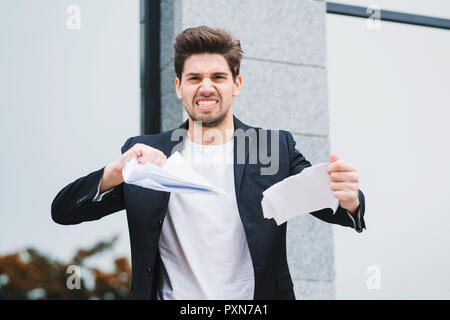 Serious businessman tearing contract in pieces. Angry furious male office worker throwing crumpled paper, having nervous breakdown at work, screaming in anger, stress management. - Stock Photo