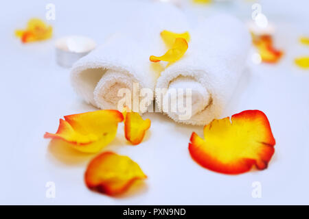 Two towels and rose petals in the spa salon - Stock Photo