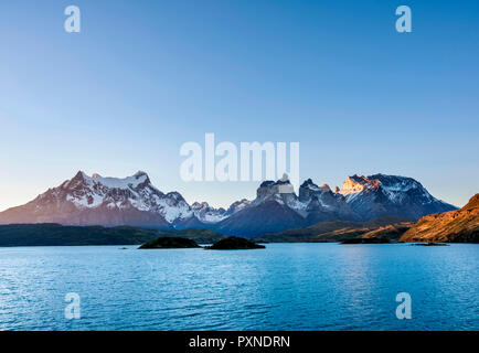 View over Lake Pehoe towards Paine Grande and Cuernos del Paine, sunset, Torres del Paine National Park, Patagonia, Chile - Stock Photo