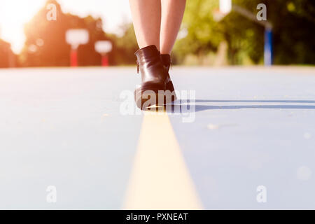 Legs of a woman wearing ankle boots walking on a line  on sports ground - Stock Photo