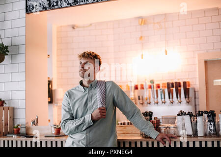 Young man working in his start-up cafe, standing at bar, daydreaming