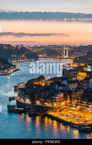 Portugal, Norte region, Porto (Oporto). Douro river banks at dusk with Arrabida bridge in the background. - Stock Photo