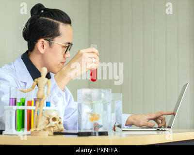 Asian scientist wearing eyeglassess holding tube contain red liquid witht Siam fighting fish in tank while recording testing result in notebook - Stock Photo