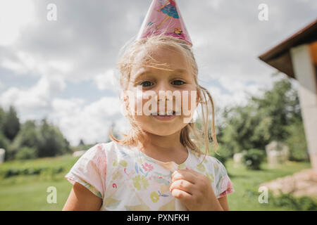 Portrait of smiling little girl wearing paper cone