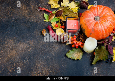 pumpkin, candle, chestnut in the shell,  in a glass and autumnal fallen maple leaves on the dark background, fall still life, autumn concept - Stock Photo