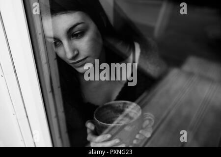 Portrait of young woman with cup of tea looking out of the window - Stock Photo