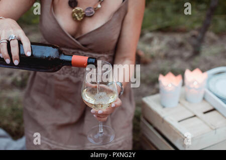 Woman pouring wine in glass on a picnic in nature - Stock Photo