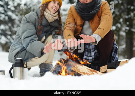 Close-up of travelers in puffy jackets sitting by campfire and warming hands at winter camping - Stock Photo