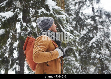 Content inspired handsome young man in warm hat and scarf traveling alone and contemplating forest around in winter - Stock Photo