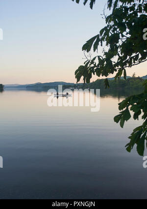 Men fishing in a rowing boat on Coniston Water the Lake District National Park, at dusk, Cumbria, England, UK, GB - Stock Photo