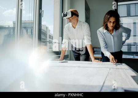 Two architects working on blueprints, man using VR glasses
