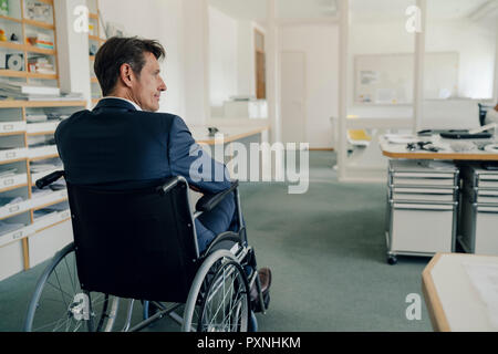 Disabled businessman sitting in wheelchair - Stock Photo