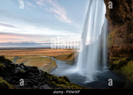 Seljalandsfoss waterfall along Iceland's southern coast is fed by melting water from the famed glacier-capped Eyjafjallajokull volcano. The 65 meter h - Stock Photo